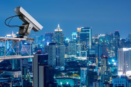 při pohledu na fotoaparát: Bezpečnostní kamera detekuje pohyb dopravy. Mrakodrap na střeše. Reklamní fotografie