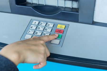 Someone pressing number button on ATM machine Stock Photo