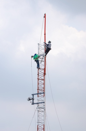 Employees are installing an antenna for transmission. photo