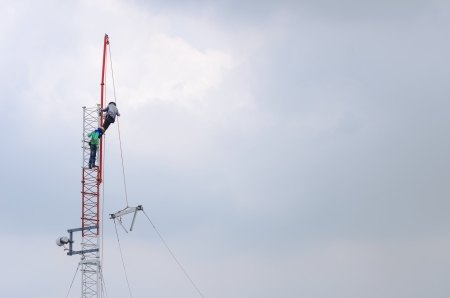 Employees are installing an antenna for transmission. Stock Photo