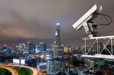 detects: Security camera detects the movement of traffic. Skyscraper rooftop.