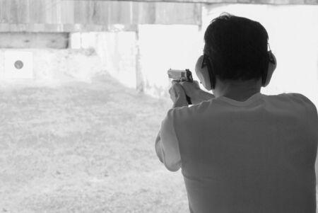 Man shooting at a target on an outdoor shooting range. photo