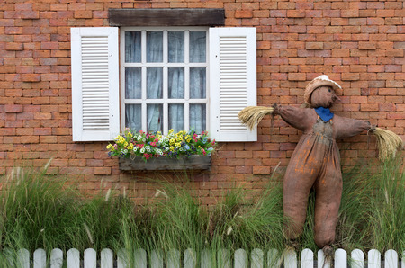White window on a red brick wall with a scarecrow. photo
