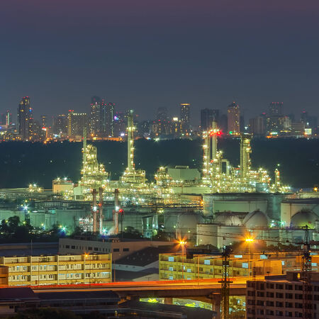 Panoramic view of the oil refinery. The backdrop is a skyscraper business district. Twilight time photo