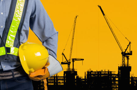 Engineer holding yellow helmet for workers security on background of new highrise apartment buildings and construction cranes on background of evening sunset cloudy sky Silhouette Crane lifts load.