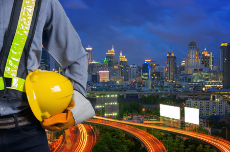 Engineer holding a yellow helmet for the safety of the workers, with expressway as a backdrop and modern building in the business district twilight time.
