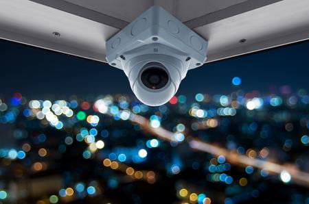 높은 건물 발코니에 보안 카메라. 흐리게 빛으로 밤 도시보기 스톡 콘텐츠