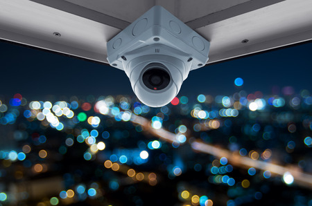 The security cameras on a balcony high building. City view at night with blurred light