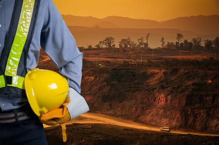 Ingeniero que sostiene un casco amarillo para la seguridad de los trabajadores en un fondo de camiones de minería de carbón están conduciendo en la carretera. El atardecer