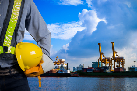 Engineer holding a yellow helmet for the safety of workers on the background stock port with cranes and containers. Archivio Fotografico