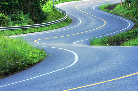 one lane street sign: The winding road on the mountain in the country. Stock Photo