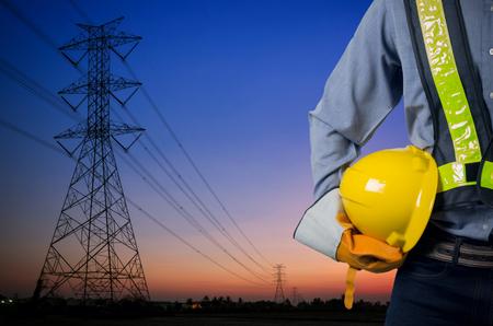 배경에 노동자의 안전을 위해 노란 헬멧을 들고 엔지니어. 저녁 태양의 배경에 실루엣 전송 타워.