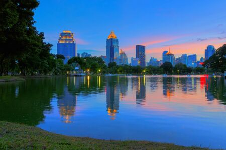 lumpini: Buildings that reflect the business landscape lake in the park, Lumpini Park, Bangkok, Thailand. Stock Photo