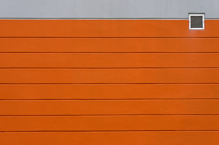 louver: Orange and gray concrete wall. With small vents For background