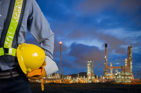 배경 정유 공장에 근로자의 안전을 위해 노란색 헬멧을 들고 엔지니어. 새벽에 아름다운 하늘