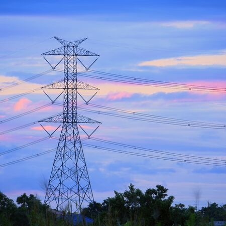 over voltage: Beautiful sunset scene in twilight blue sky with beautiful clouds over High voltage pole.