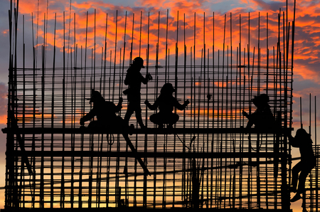 laborers: Silhouettes of laborers Buildings and structures were built. Stunning sunset sky. Stock Photo