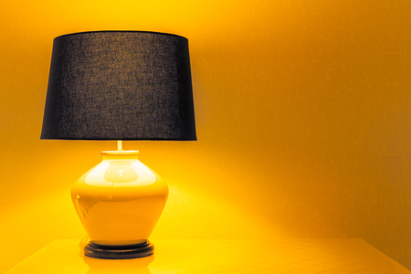 night table: Lamp on a night table next to a bed. Stock Photo