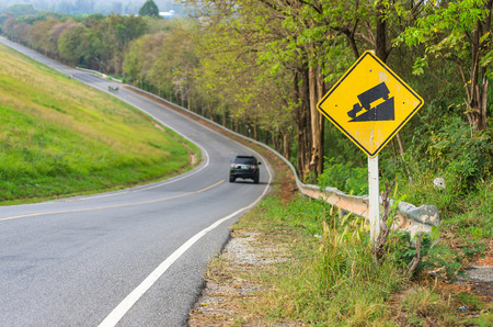 gear  speed: Traffic alerts downhill slope. Reduce speed and use a lower gear. Drive with caution. Stock Photo