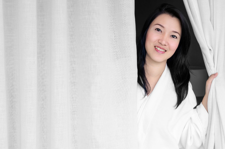 a white robe: Asian woman smiling wearing a white robe, opened the curtains in the room.