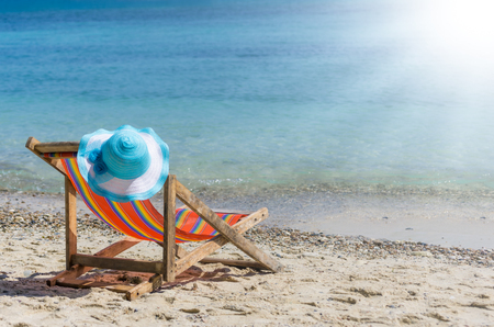 Empty colorful beach chairs and sun hat on the beach, clear, blue sky. Stok Fotoğraf
