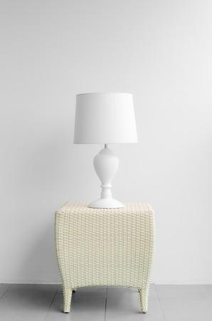 Tischlampe auf dem Schreibtisch mit weißer Wand.