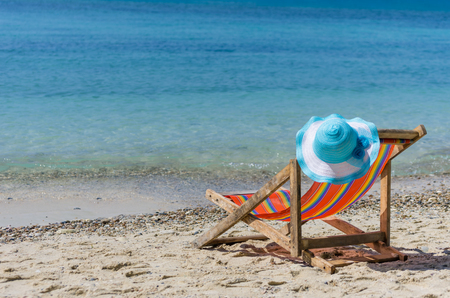 chairs: Empty colorful beach chairs and sun hat on the beach, clear, blue sky. Stock Photo