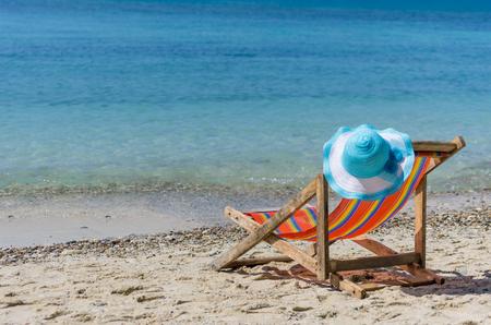 Lege kleurrijke strandstoelen en zonnehoed op het strand, heldere, blauwe hemel.