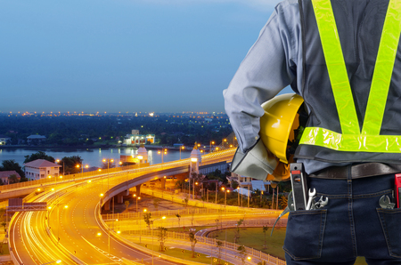 Engineers holding a yellow helmet for the safety of workers with a bridge over the river as a backdrop, During the twilight sky. Stock Photo