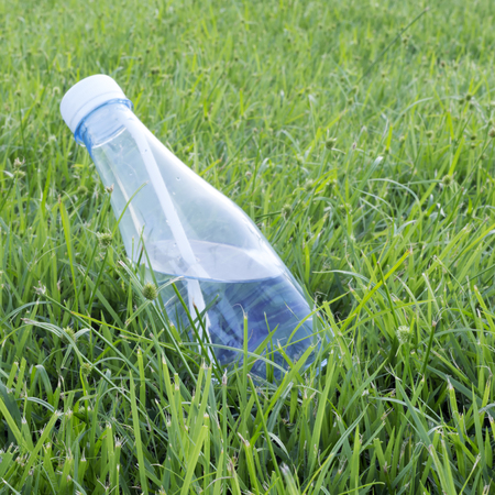 Water bottles on the green grass in the park. Stock Photo