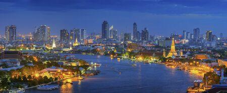 wat arun: Panorama Views of Bangkok and the Chao Phraya River Wat Arun curve. Against a backdrop of high-rise buildings at dusk.