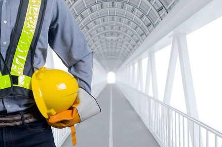 Engineer holding yellow helmets for the safety of workers at a structured pathway white backdrop.