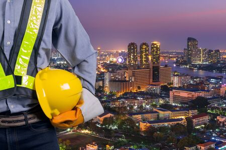Engineer holding a yellow helmet for safety of the workers. A modern high-rise structures in the background. Stock Photo