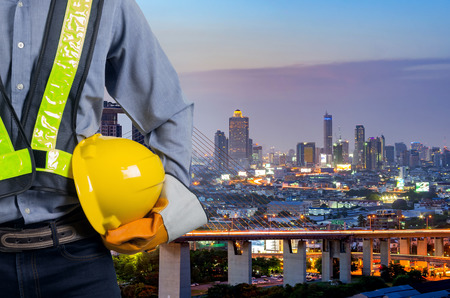 Engineer holding a yellow helmet with a backdrop of the city and industry.
