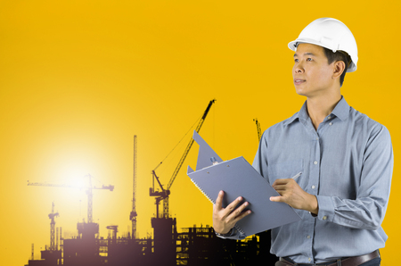 ingenieria industrial: Engineer holding a white helmet for the safety of construction workers on a background crane Silhouette sunset.