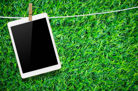 Hanging blank digital tablet computer with isolated screen with clipping path. Stock Photo