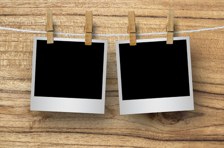 white polaroids: Blank photo frame with clothespin hanging on wooden background, with clipping path. Stock Photo
