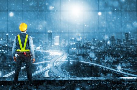 노동자의 안전을 위해 노란색 헬멧을 들고 엔지니어의 이중 노출. strom와 함께 백그라운드에서 현대적인 고층 구조. 스톡 콘텐츠