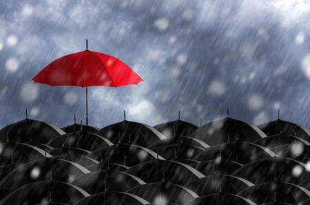 Red umbrella in mass of black umbrellas. Stock Photo