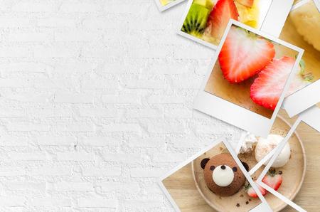Fruit de fraises dans des papiers photo sur fond de mur en briques blanches.