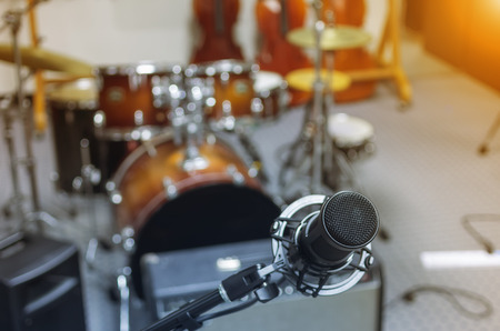 dentro fuera: Microphone in a recording studio or concert hall with drum in out of focus background. Foto de archivo