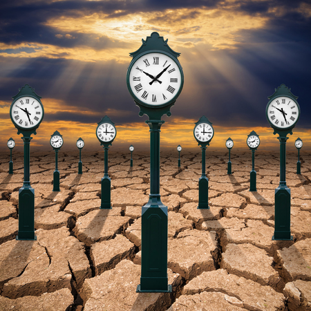 Clock pole on the ground to dry, cracked soil, concept of time changes. Stock Photo