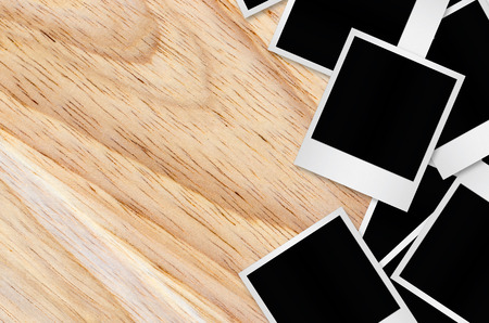 white polaroids: Blank photo papers isolated on wooden background with clipping path. Stock Photo