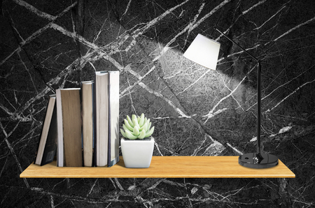 Top wooden shelves with cactus,book,table lamp and marble wall background - For product display. Stock Photo