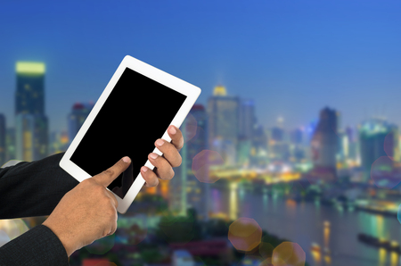 Businessman using tablet pc and city landscape at background. Stock Photo