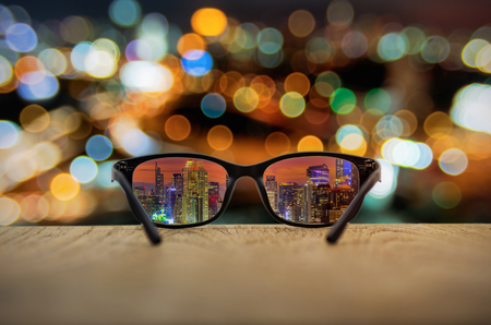 Clear cityscape focused in glasses lenses with blurred cityscape background.