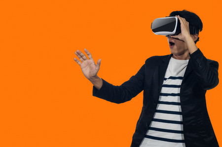 Young man with a virtual reality headset stand on orange background indoor. Standard-Bild