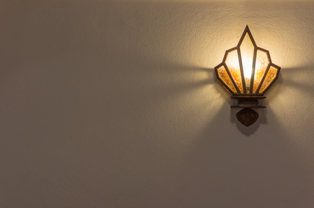 Wall lamp with yellow shade from glass with copy space. Stock Photo