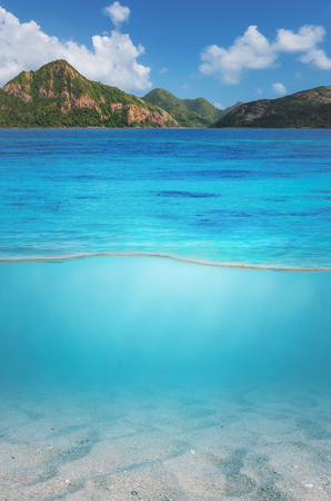 Split views above and below the surface of the sea to the mountain top and sand underwater.