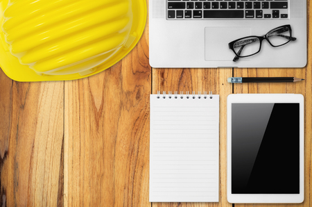 Top view desk engineer with yellow helmet, smart phone, coffee cup, paper note, glasses and office equipment. Stock Photo